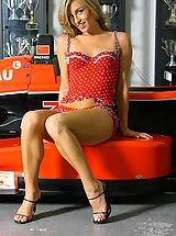 Melanie in red dotty lingerie by a racing car.