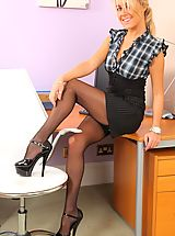 Sexy blonde in a tight black top, pinstripe pencil skirt and kinky killer heels.