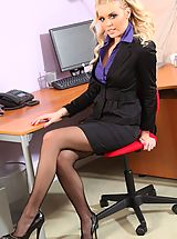 Busty Secretary, Porchia W in a smart black skirt suit and heels.