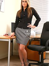 Candice wearing a black blouse with a grey skirt and grey stockings.