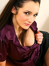 Brunette posing as a secretary in a purple silk blouse with a black miniskirt.
