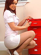 Naughty Office, Kinky redhead teases her way out of her work clothes and poses over her desk.