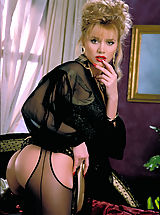 Lingerie Pics: Beautiful blonde Brittany Shaw gets cumfy cozy on a silk bed in sexy black crotchless stockings.